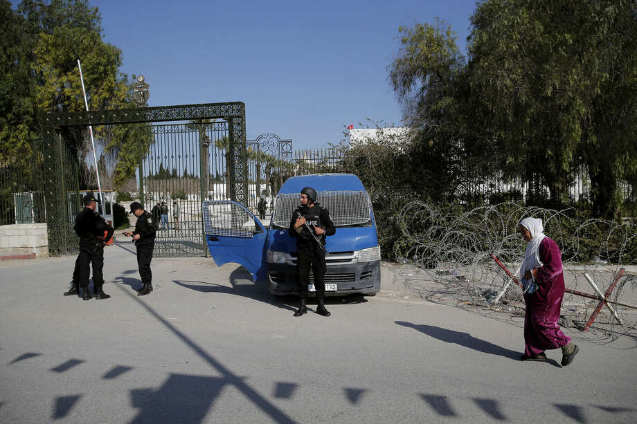 A woman walks past police officers standing guard outside the National Bardo Museum in Tunis, Thursday, March 19, 2015. Tunisian security forces arrested nine people linked to the deadly attack on the National Bardo Museum that left scores dead and wounded and threatened the country's fledgling democracy and struggling tourism industry, the president's office said Thursday. (AP Photo/Christophe Ena)