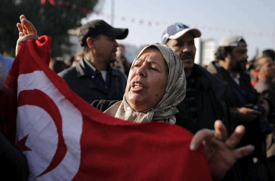 A woman holds a Tunisian national flag as she demonstrates in front of the National Bardo Museum a day after gunmen attacked the museum and killed scores of people in Tunis, Tunisia, Thursday, March 19, 2015. The Islamic State group issued a statement Thursday claiming responsibility for the deadly attack on Tunisia's national museum that killed scores of people, mostly tourists. (AP Photo/Christophe Ena)