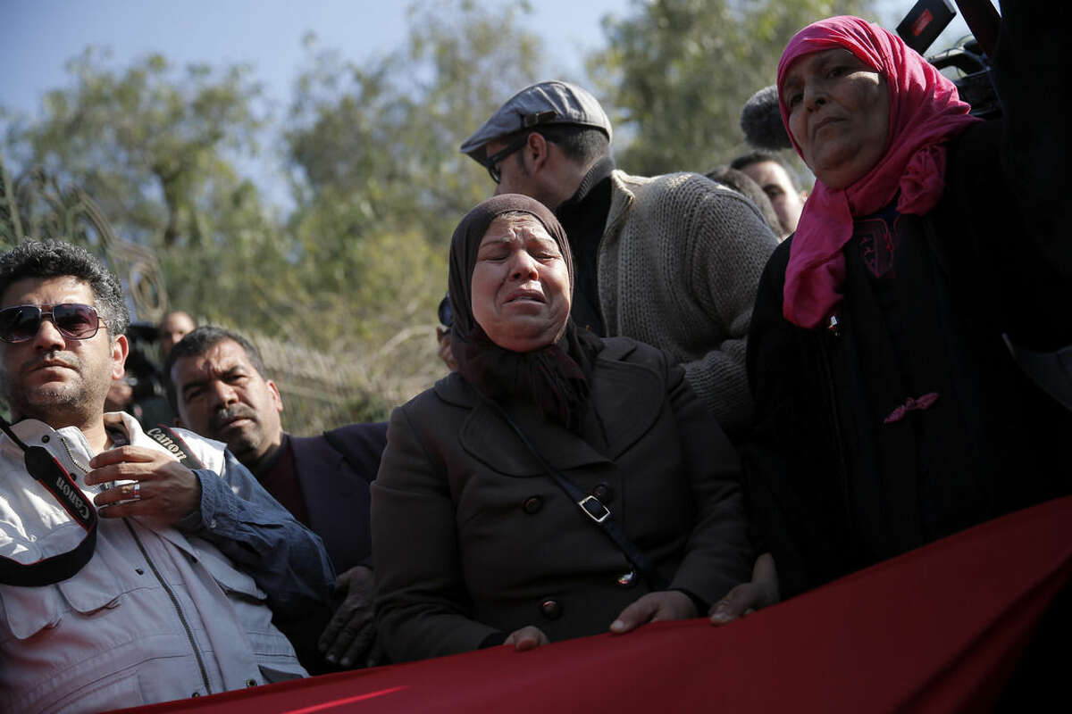 A woman cries as she demonstrates in front of the National Bardo Museum a day after gunmen attacked the museum and killed scores of people in Tunis, Tunisia, Thursday, March 19, 2015. The Islamic State group issued a statement Thursday claiming responsibility for the deadly attack on Tunisia's national museum that killed scores of people, mostly tourists. (AP Photo/Christophe Ena)