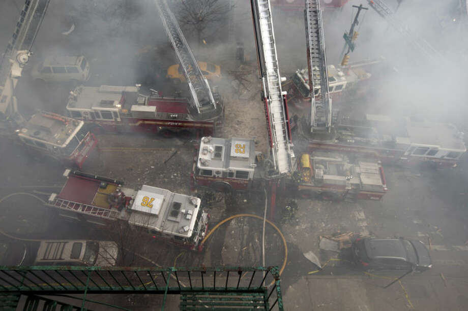 Firefighters respond to a fire on 116th Street in Harlem after a building exploded in huge flames and billowing black smoke, leading to the collapse of at least one building and several injuries, Wednesday, March 12, 2014, in New York. (AP Photo/John Minchillo)