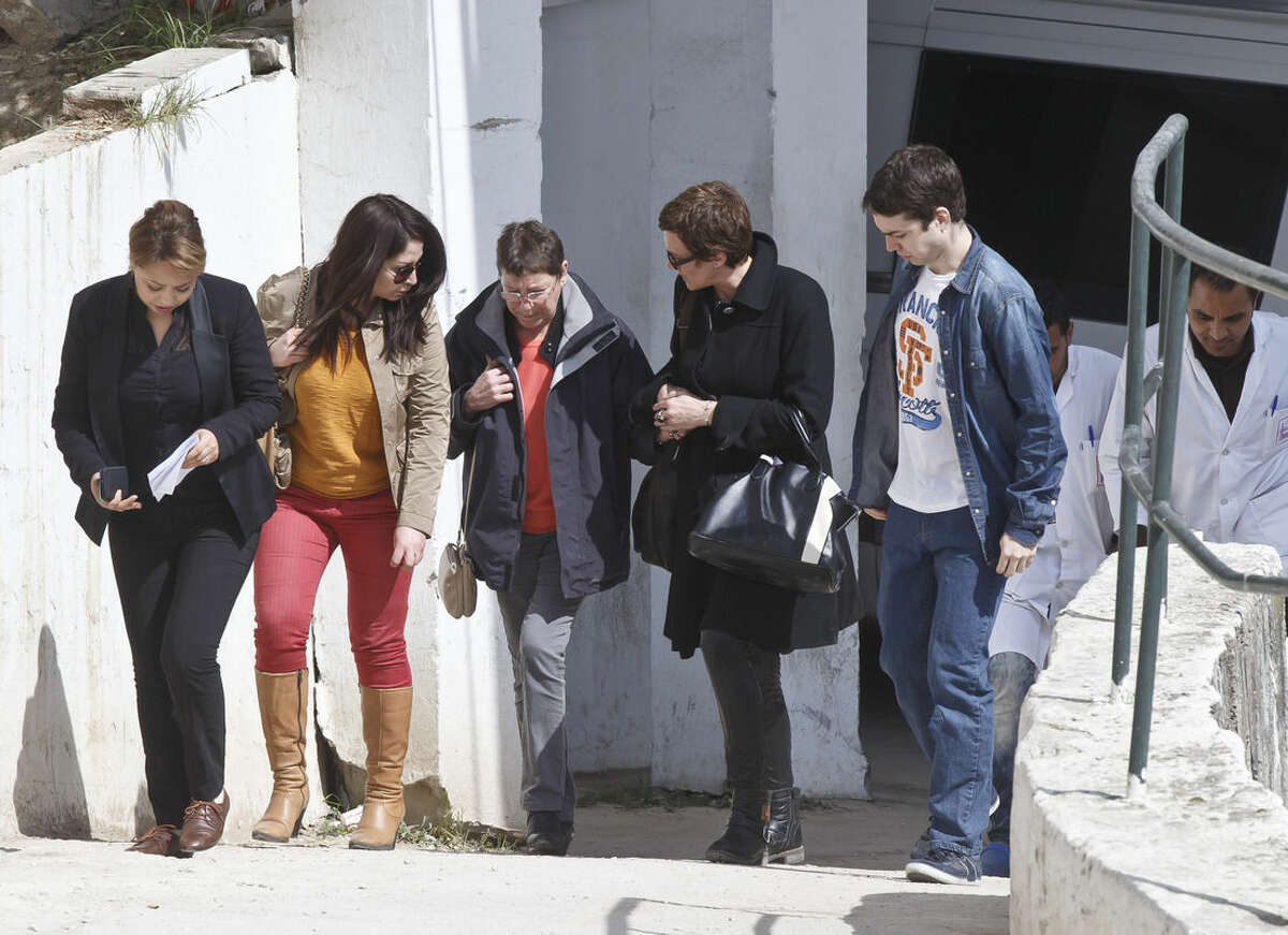 A unidentified relative of a victim of the attack, center, is escorted at the morgue of the Charles Nicolle hospital in Tunis Tunisia, Thursday, March 19, 2015. Authorities said more than 20 were killed after an attack on a major museum in the Tunisian capital, and some of the gunmen may have escaped. (AP Photo/Michel Euler)