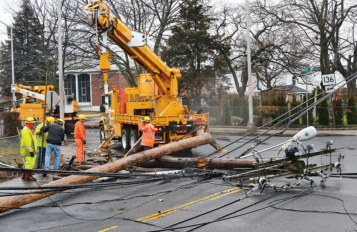 Hour photo / Erik Trautmann Eversource workers fix a utlity pole that was fell by a two car accident on Quintard Ave and Route 136 just after midnight Tuesday shutting down traffic in South Norwalk.