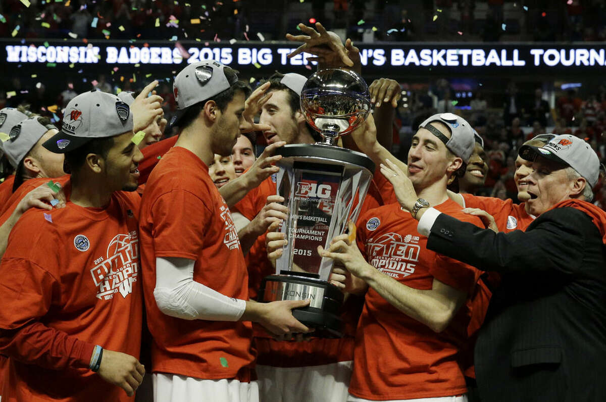 Wisconsin players celebrate with the trophy after winning the Big Ten tournament in an NCAA college basketball game in Chicago, Sunday, March 15, 2015. Wisconsin defeated Michigan State 80-69 in overtime. (AP Photo/Nam Y. Huh)