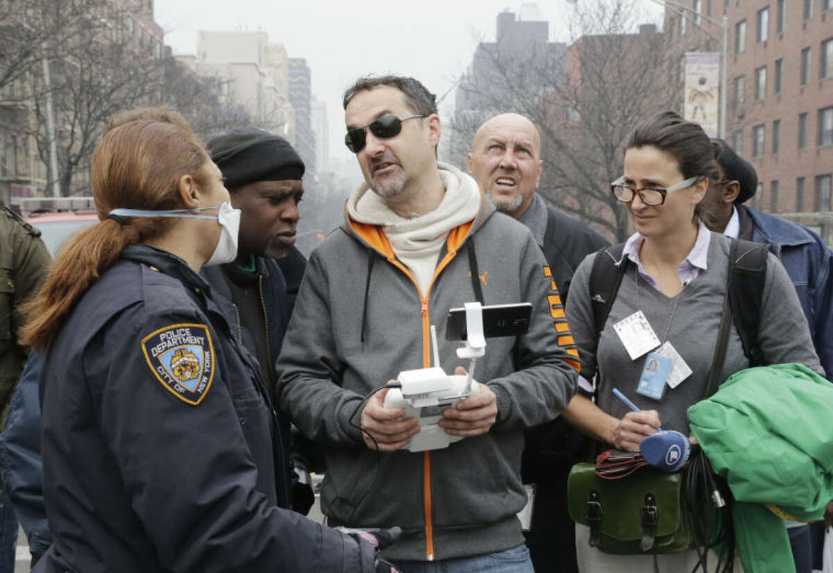 A New York City police officer, left, tells Brian Wilson, center, to land the drone that he was flying over the scene of an explosion that leveled two apartment buildings in East Harlem, Wednesday, March 12, 2014 in New York. Wilson says he uses the aerial drone to document buildings, weddings and news events. (AP Photo/Mark Lennihan)