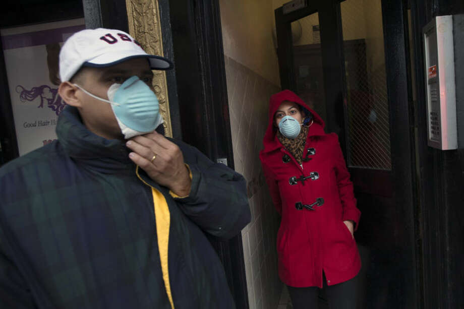 Pedestrians wear masks as smoke surrounds the perimeter after an explosion leveled two apartment buildings in the East Harlem neighborhood of New York, Wednesday, March 12, 2014. Con Edison spokesman Bob McGee says a resident from a building adjacent to the two that collapsed reported that he smelled gas inside his apartment, but thought the odor could be coming from outside. (AP Photo/John Minchillo)