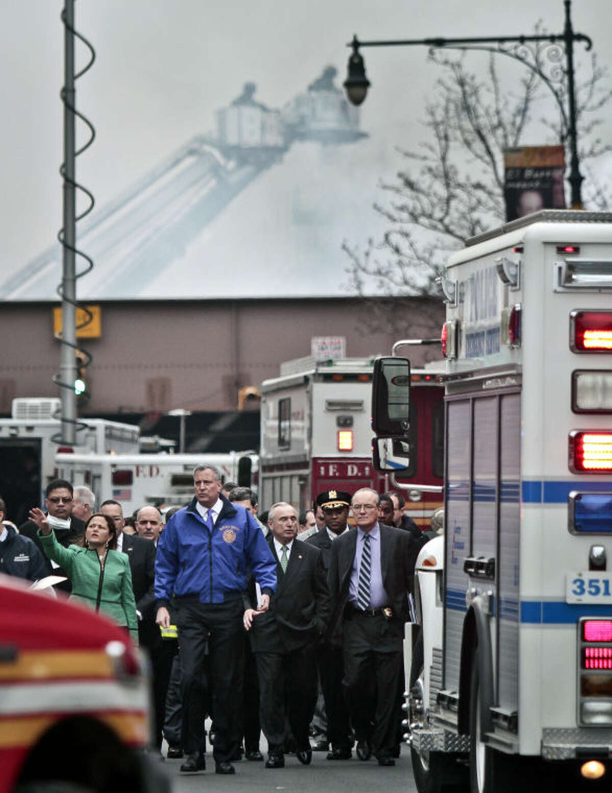 New York city council speaker Melissa Mark-Viverito, second from left, and New York Mayor Bill de Blasio, center, lead a group of city officials to a news conference after visiting the site of an explosion that leveled two apartment buildings in Harlem, Wednesday March 12, 2014 in New York. (AP Photo/Bebeto Matthews)