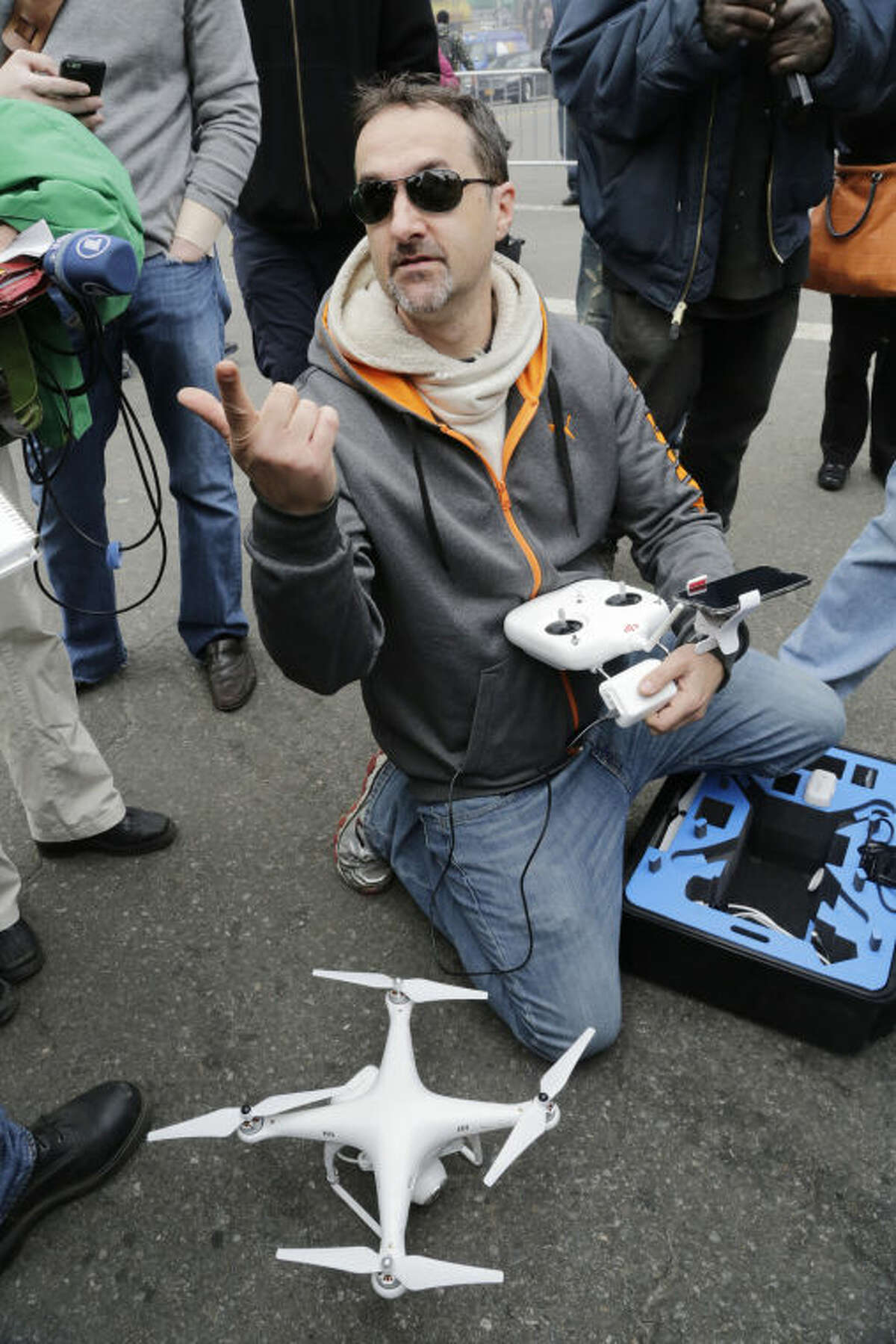 Brian Wilson packs away the drone that he was flying to video the scene of an explosion that leveled two apartment buildings in East Harlem, Wednesday, March 12, 2014, in New York. Wilson says he uses the aerial drone to document buildings, weddings and news events. (AP Photo/Mark Lennihan)