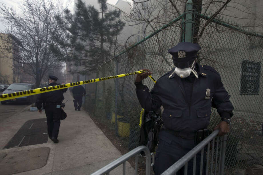 Police officers patrol the perimeter of the scene after an explosion leveled two apartment buildings in the East Harlem neighborhood of New York, Wednesday, March 12, 2014. The blast happened after a neighbor reported smelling natural gas. (AP Photo/John Minchillo)