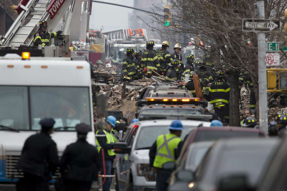 Firefighters respond to an explosion that leveled two apartment buildings in the East Harlem neighborhood of New York, Wednesday, March 12, 2014. Con Edison spokesman Bob McGee says a resident from a building adjacent to the two that collapsed reported that he smelled gas inside his apartment, but thought the odor could be coming from outside. (AP Photo/John Minchillo)