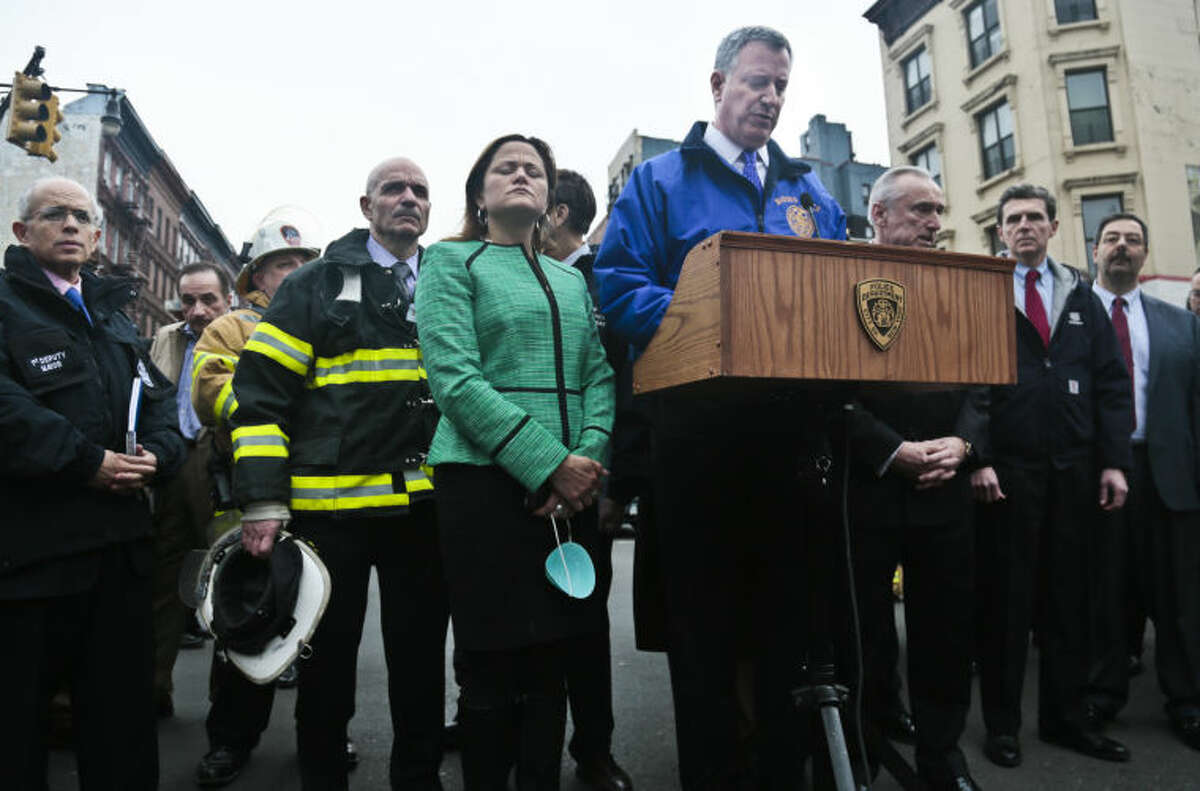 New York City Mayor Bill de Blasio, center, speaks as a group of city officials look on during a news conference after visiting the site of an explosion that leveled two apartment buildings in Harlem, Wednesday March 12, 2014 in New York. (AP Photo/Bebeto Matthews)