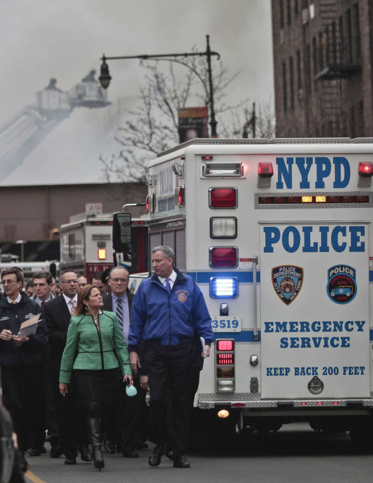 New York city council speaker Melissa Mark-Viverito, center, and New York Mayor Bill de Blasio, right, lead a group of city officials to a news conference after visiting the site of an explosion that leveled two apartment buildings in Harlem, Wednesday March 12, 2014 in New York. (AP Photo/Bebeto Matthews)