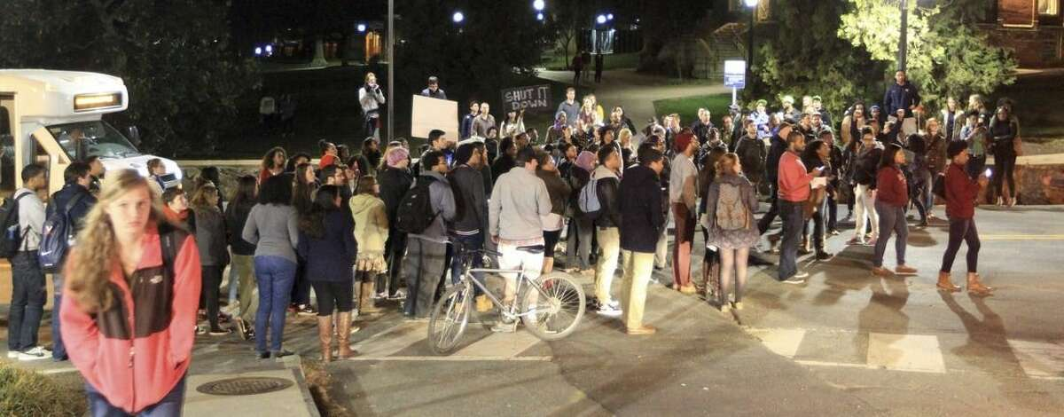 About a hundred students blocked traffic on University Avenue protesting for fellow Virginia student Martese Johnson Wednesday, March 18, 2015, in Charlottesville, Va. Johnson was bloodied during an arrest Wednesday about 1 a.m. by State Alcoholic Beverage Control agents outside Trinity Irish Pub on the Corner. (AP Photo/The Daily Progress, Andrew Shurtleff)