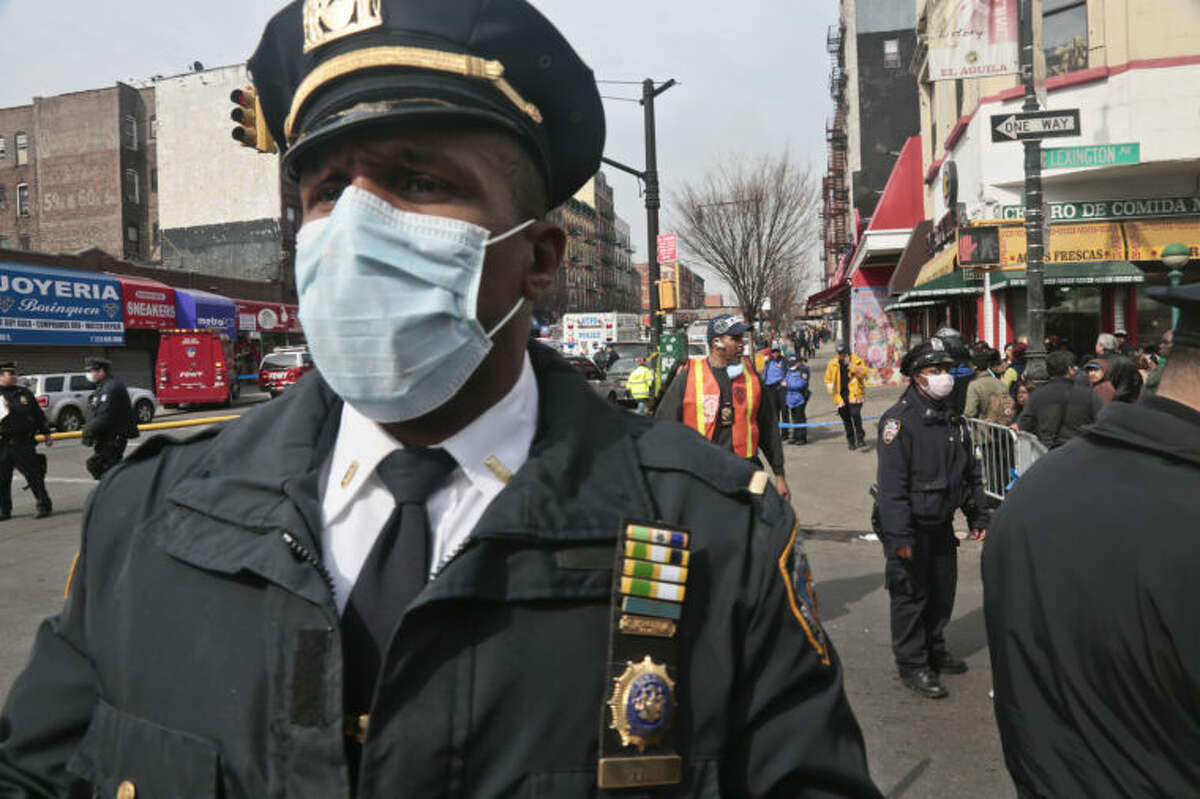 A police officers wear safety mask a block away from the site of an explosion that leveled two apartment buildings in the East Harlem neighborhood of New York, Wednesday, March 12, 2014. Con Edison spokesman Bob McGee says a resident from a building adjacent to the two that collapsed reported that he smelled gas inside his apartment, but thought the odor could be coming from outside. (AP Photo/Bebeto Matthews)
