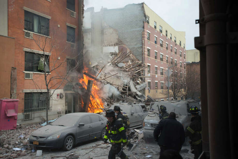 Firefighters work the scene of an explosion that leveled two apartment buildings in the East Harlem neighborhood of New York, Wednesday, March 12, 2014. Con Edison spokesman Bob McGee says a resident from a building adjacent to the two that collapsed reported that he smelled gas inside his apartment, but thought the odor could be coming from outside. (AP Photo/Jeremy Sailing)