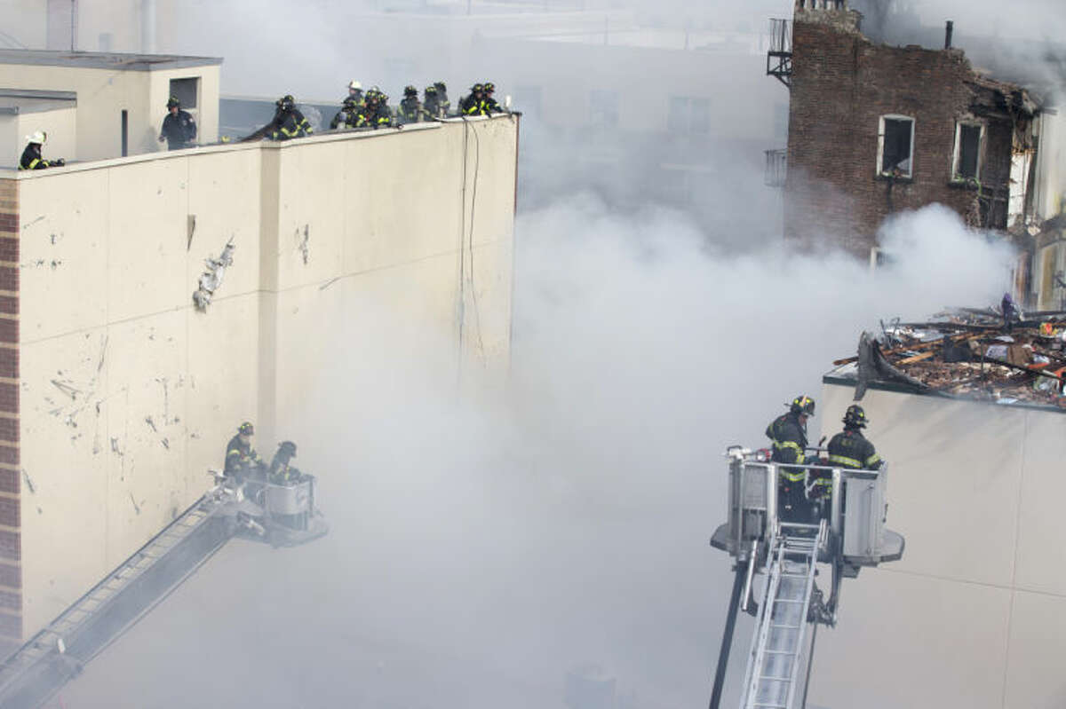 Firefighters respond to a fire after an explosion and building collapse in the East Harlem neighborhood of New York, Wednesday, March 12, 2014. The explosion leveled an apartment building, and sent flames and billowing black smoke above the skyline. (AP Photo/John Minchillo)