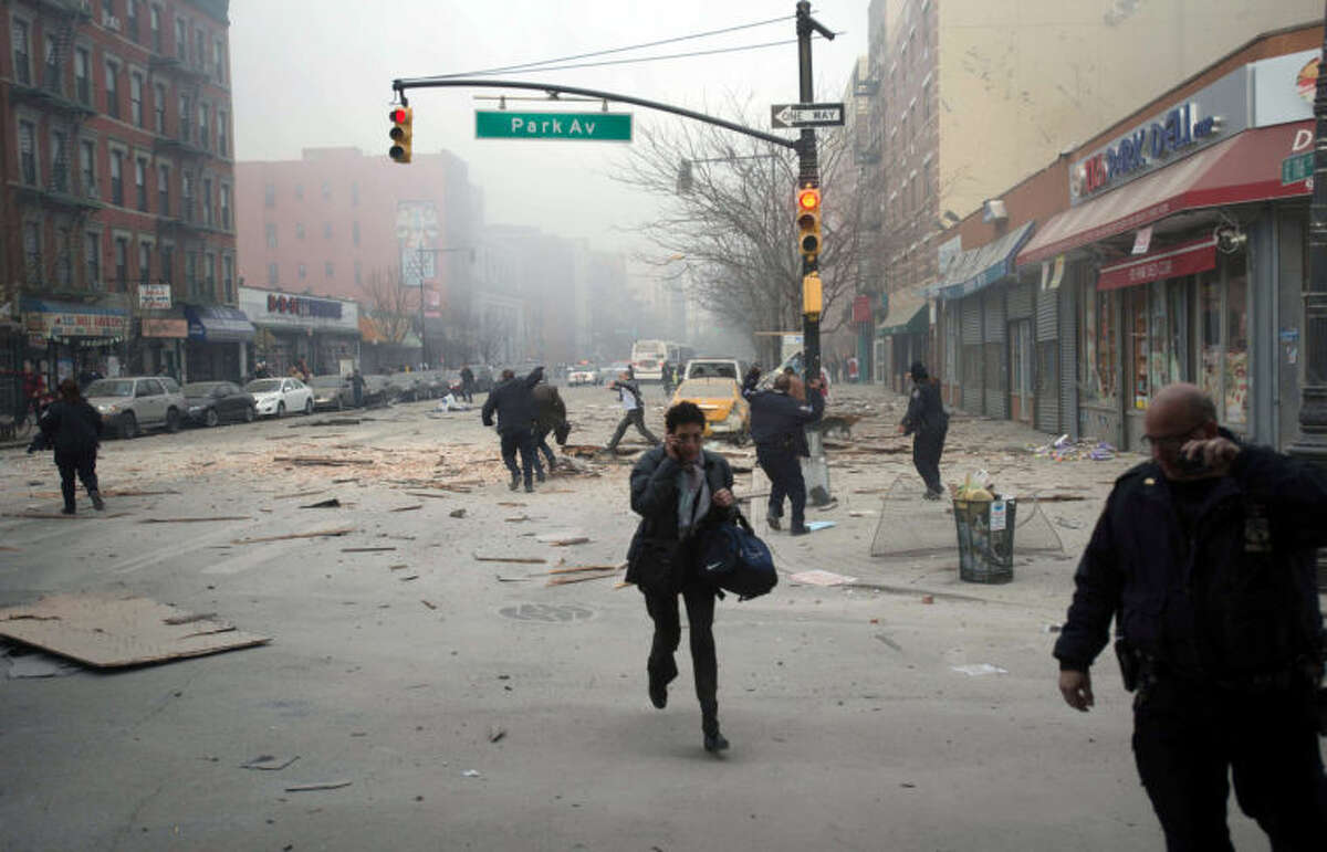 People run after an explosion and building collapse in the East Harlem neighborhood of New York, Wednesday, March 12, 2014. The explosion leveled an apartment building, and sent flames and billowing black smoke above the skyline. (AP Photo/Jeremy Sailing)