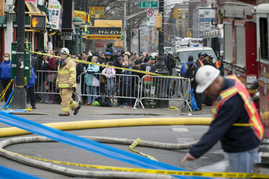 Firefighters respond to an explosion and building collapse in the East Harlem neighborhood of New York, Wednesday, March 12, 2014. The explosion leveled an apartment building, and sent flames and billowing black smoke above the skyline. (AP Photo/John Minchillo)