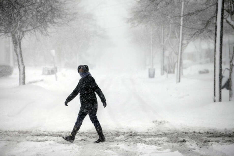 A woman crosses the street through the snow, Wednesday, March 12, 2014, in Bowling Green, Ohio. A winter storm warning was in effect Wednesday for much of northern Ohio, where 4 to 8 inches of snow are expected. (AP Photo/Sentinel-Tribune, J.D. Pooley) MANDATORY CREDIT, TOLEDO BLADE OUT