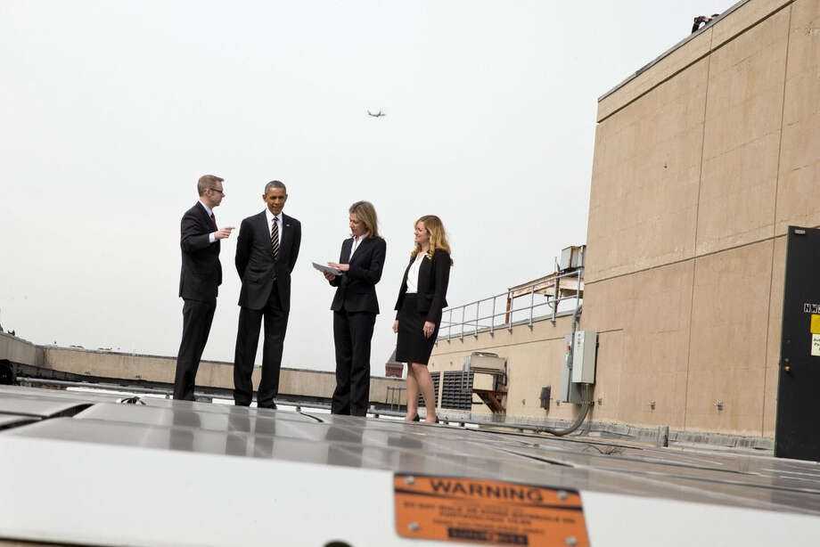 A plane flies overhead and a Secret Service guards above, as President Barack Obama tours solar panels on the roof of the Energy Department in Washington, Thursday, March 19, 2015. From left are, Eric Haukdal, Energy Department Energy Manager, the president, Deputy Energy Secretary Liz Sherwood-Randall and Kate Brandt, Federal Chief Sustainability Officer. (AP Photo/Jacquelyn Martin)