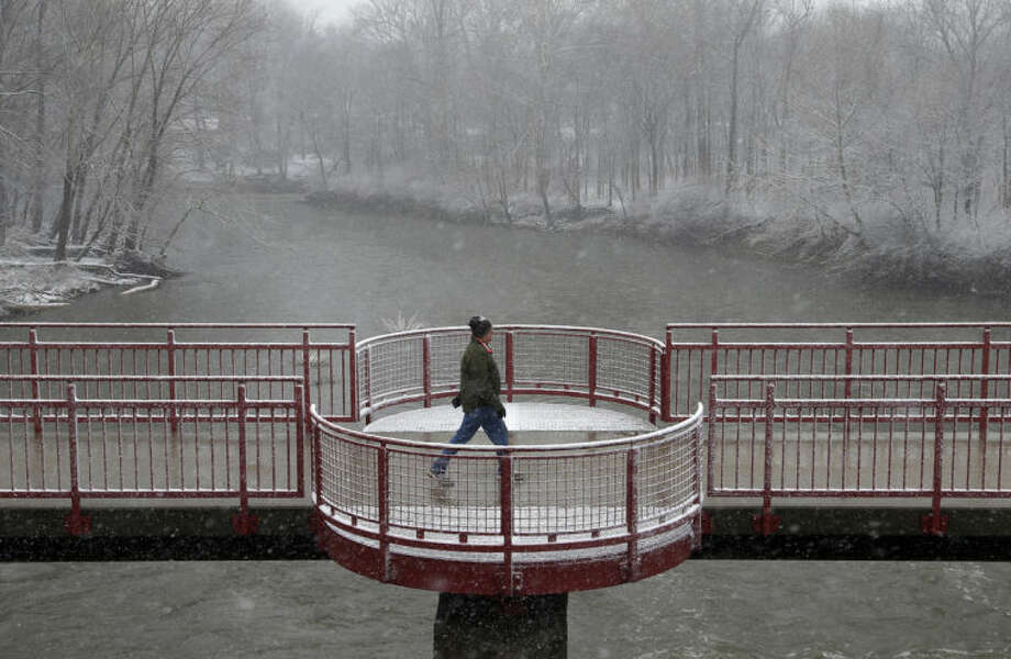 A man makes his was across a bridge spanning the White River as snow falls in Indianapolis, Wednesday, March 12, 2014. Snow fell in central Indiana with accumulation of less than 1 inch. (AP Photo/Michael Conroy)
