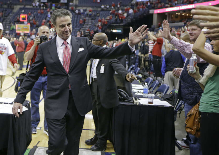Louisville coach Rick Pitino waves to fans as he leaves the court after Louisville defeated Connecticut 71-61 in an NCAA college basketball game in the final of the American Athletic Conference men's tournament Saturday, March 15, 2014, in Memphis, Tenn. (AP Photo/Mark Humphrey)