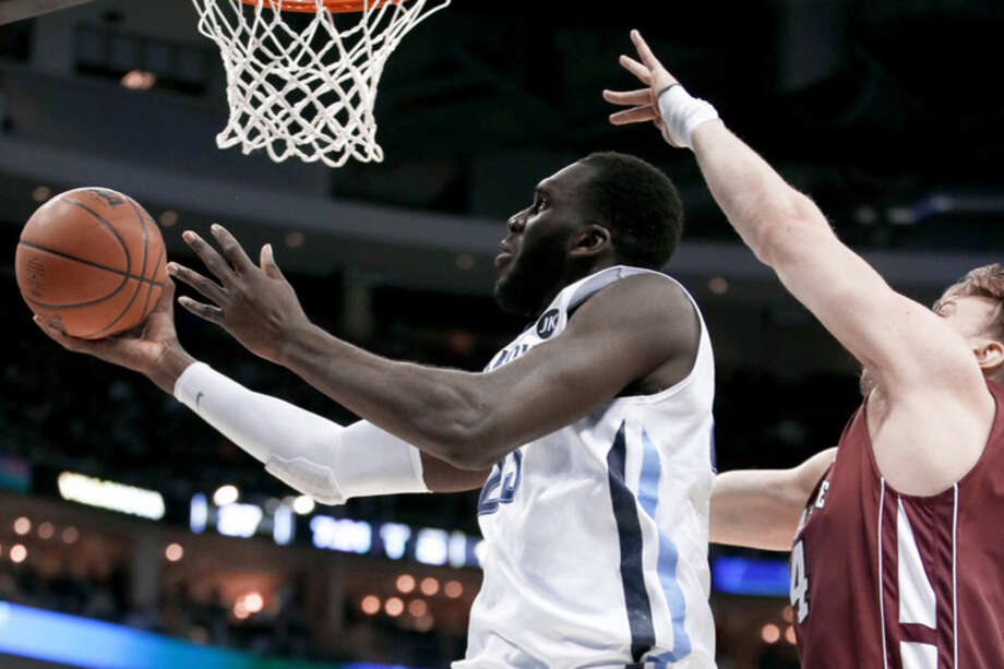 Villanova's Daniel Ochefu, left, shoots past Lafayette's Bryce Scott during the first half of an NCAA tournament second round college basketball game, Thursday, March 19, 2015, in Pittsburgh. (AP Photo/Gene J. Puskar)