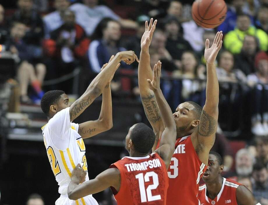 Virginia Commonwealth guard Terry Larrier, left, passes off against Ohio State center Amir Williams, right, and forward Sam Thompson during the first half of an NCAA college basketball tournament second round game in Portland, Ore., Thursday, March 19, 2015. (AP Photo/Greg Wahl-Stephens)