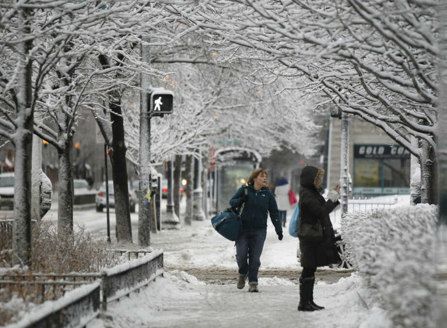 Commuters walk through snow covered sidewalks after an overnight snowstorm Wednesday, March 12, 2014, in downtown Chicago. A late winter storm dumped more than 5 inches of snow in the Chicago area, causing power outages and headaches for commuters. (AP Photo/Kiichiro Sato)