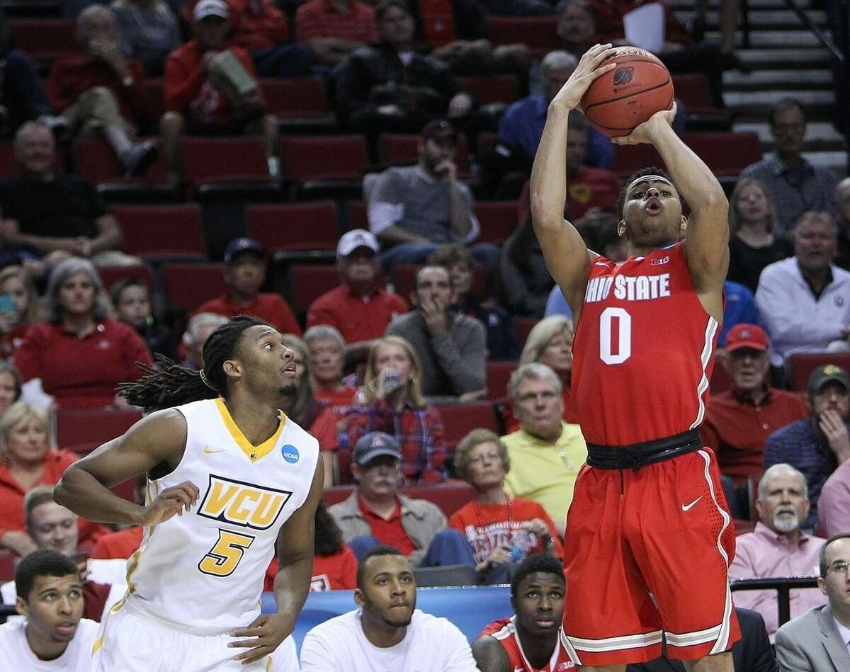 Ohio State guard D'Angelo Russell, right shoots as Virginia Commonwealth guard Doug Brooks watches during the second half in the second round of the NCAA college basketball tournament in Portland, Ore., Thursday, March 19, 2015. (AP Photo/Craig Mitchelldyer)