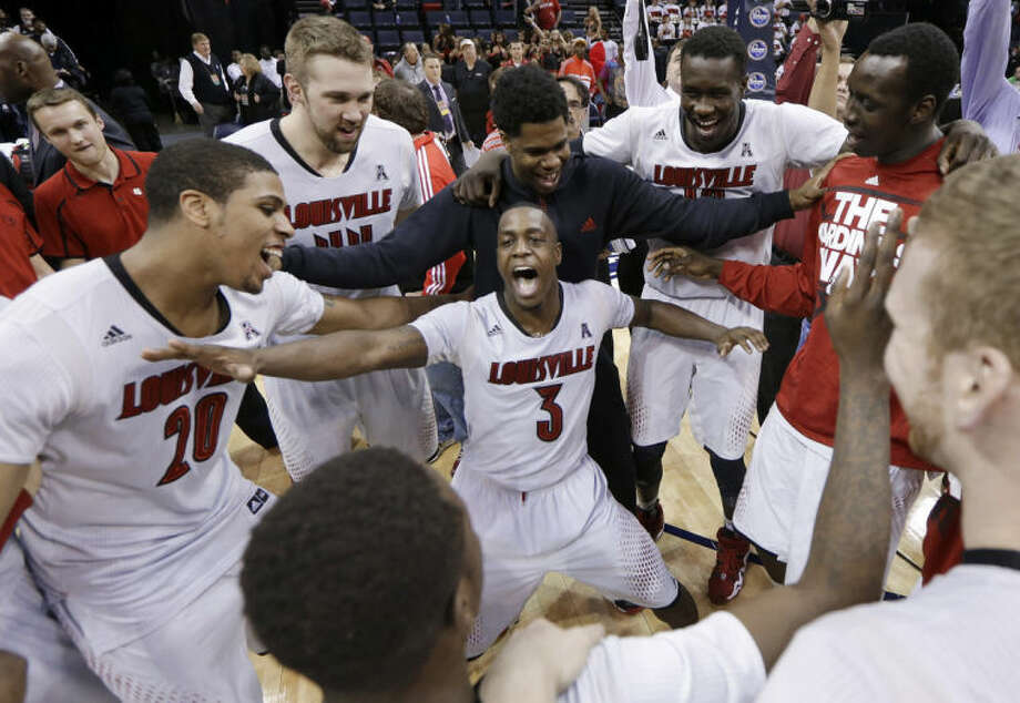 Louisville players, including Chris Jones (3) and Wayne Blackshear (20), celebrate after defeating Connecticut 71-61 in an NCAA college basketball game in the finals of the American Athletic Conference tournament Saturday, March 15, 2014, in Memphis, Tenn. (AP Photo/Mark Humphrey)