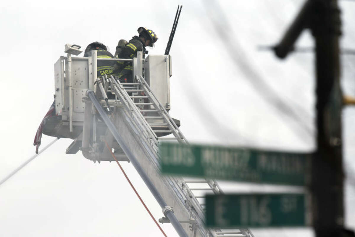 Firefighters respond after an explosion and building collapse in the East Harlem neighborhood of New York, Wednesday, March 12, 2014. The explosion leveled an apartment building, and sent flames and billowing black smoke above the skyline. (AP Photo/John Minchillo)