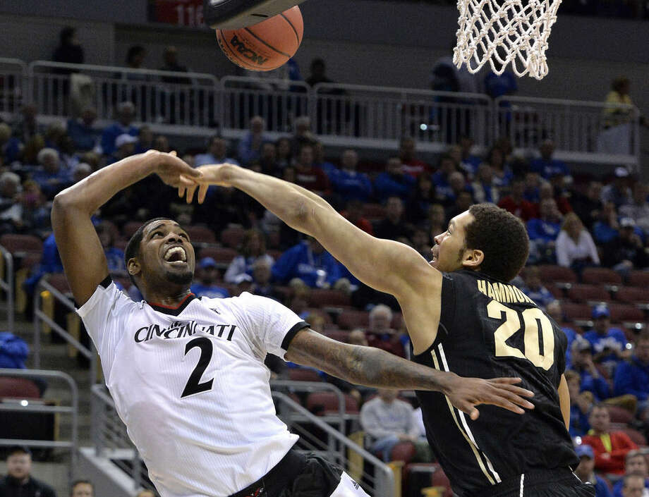 Cincinnati's Octavius Ellis, left, has his shot blocked by Purdue's A.J. Hammons during the first half of an NCAA tournament second-round college basketball game in Louisville, Ky., Thursday, March 19, 2015. (AP Photo/Timothy D. Easley)
