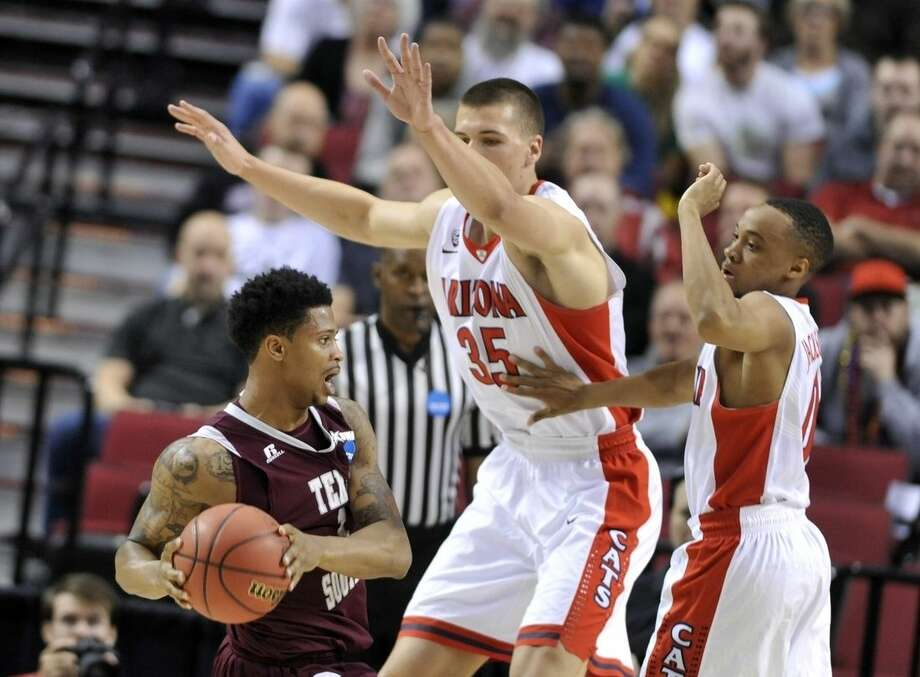 Texas Southern guard Deverell Biggs, left, is double-teamed by Arizona guard Parker Jackson-Cartwright, right, and center Kaleb Tarczewski during the first half in the second round of the NCAA college basketball tournament in Portland, Ore., Thursday, March 19, 2015. (AP Photo/Greg Wahl-Stephens)