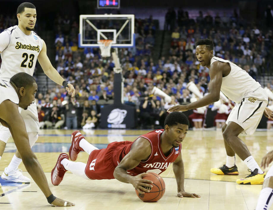 Indiana guard Robert Johnson, center, picks up a loose ball between Wichita State's Shaquille Morris, left, Fred VanVleet (23) and Zach Brown, right, during the first half of an NCAA tournament college basketball game in the Round of 64, Friday, March 20, 2015, in Omaha, Neb. (AP Photo/Charlie Neibergall)
