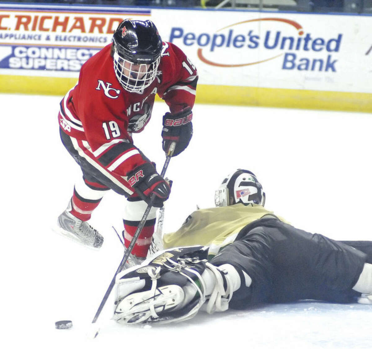Hour photo/John Nash New Canaan's Henry Stanton, left, is stoned by Notre Dame-West Haven goaltender Wade Conlan, who made a desperation kick save during a second-period breakaway in Saturday's CIAC Division I quarterfinals at the Webster Bank Arena.