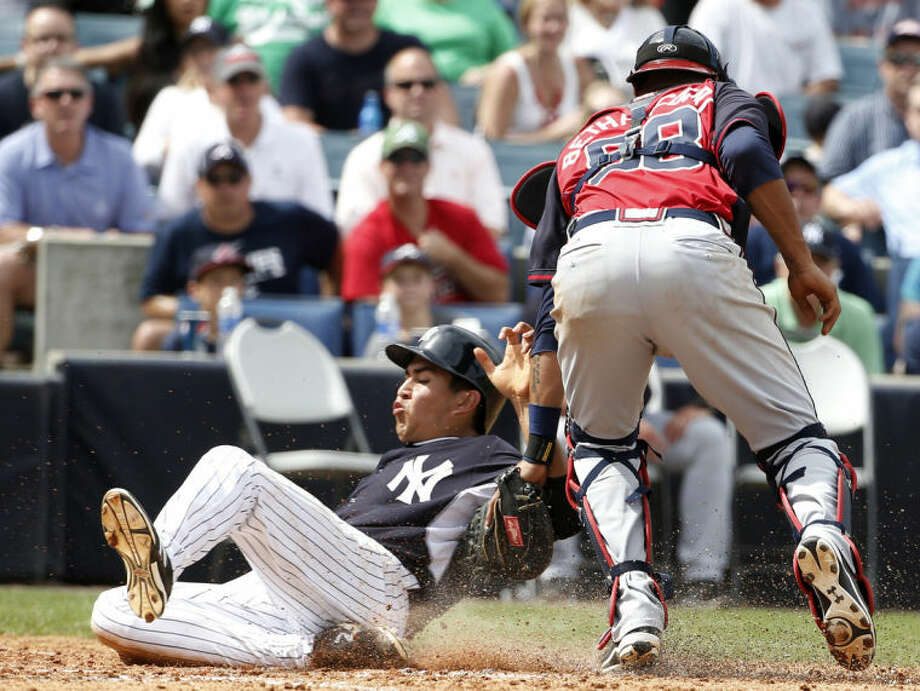 New York Yankees' Ramon Flores, left, scores as he slides past Atlanta Braves catcher Christian Bethancourt (58) in the fifth inning of a spring exhibition baseball game in Tampa, Fla., Sunday, March 16, 2014. Bethancourt lost control of the ball in the play. (AP Photo/Kathy Willens)
