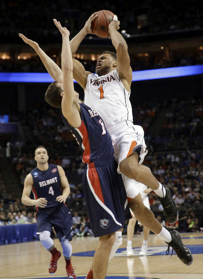 Virginia's Justin Anderson, right, drives against Belmont's Taylor Barnette, left, during the first half of an NCAA tournament college basketball game in the Round of 64 in Charlotte, N.C., Friday, March 20, 2015. (AP Photo/Gerald Herbert)