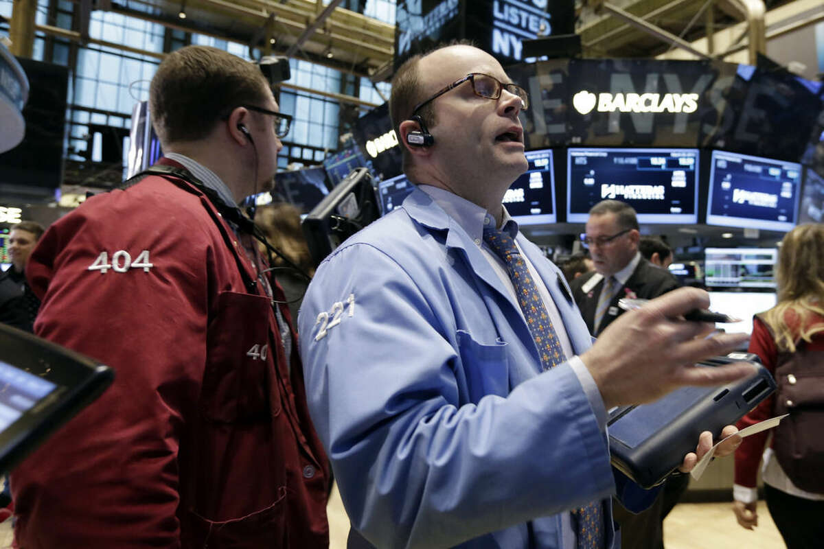Trader Peter Mancuso, right, works on the floor of the New York Stock Exchange, Friday, March 20, 2015. Stocks are moving higher in early trading as investors respond to some surprisingly strong earnings from U.S. companies. (AP Photo/Richard Drew)