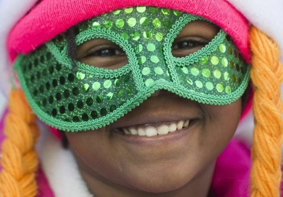 A spectator smiles as she watches the annual St. Patrick's Day parade in Montreal, Sunday, March 16, 2014. (AP Photo/The Canadian Press, Graham Hughes)