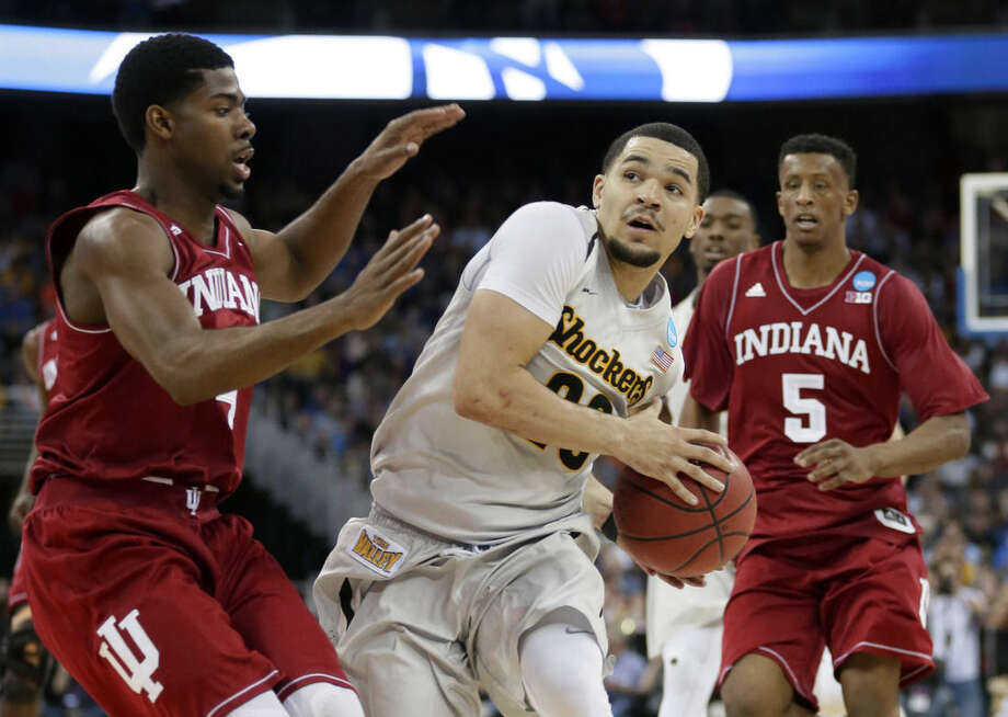 Wichita State guard Fred VanVleet, center, drives to the basket between Indiana's Robert Johnson, left, and Troy Williams (5) during the second half of an NCAA tournament college basketball game in the Round of 64, Friday, March 20, 2015, in Omaha, Neb. VanVleet scored 27 points as Wichita State won 81-76.(AP Photo/Charlie Neibergall)