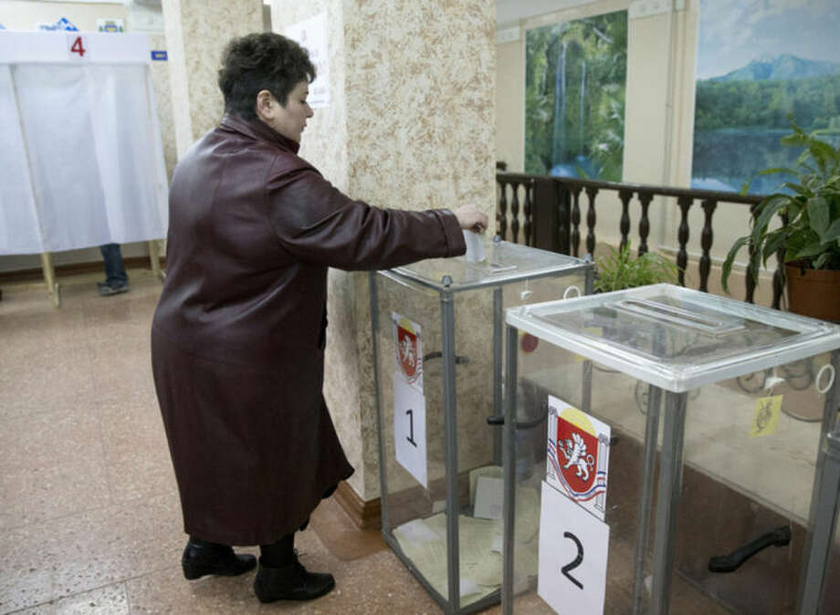A woman casts her ballot in the Crimean referendum in Simferopol, Ukraine, Sunday, March 16, 2014. Residents of Ukraine's Crimea region are voting in a contentious referendum on whether to split off and seek annexation by Russia. (AP Photo/Vadim Ghirda)
