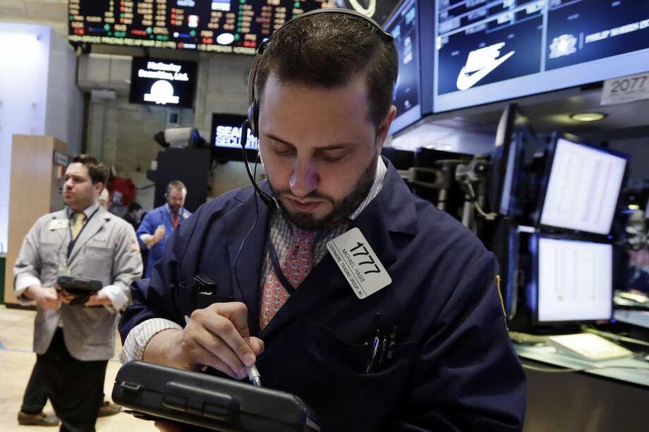 Trader Michael Hagis, center, works on the floor of the New York Stock Exchange, Friday, March 20, 2015. Nike jumped $3.63, or 3.7 percent, to $101.95 after reporting quarterly results that beat expectations. (AP Photo/Richard Drew)