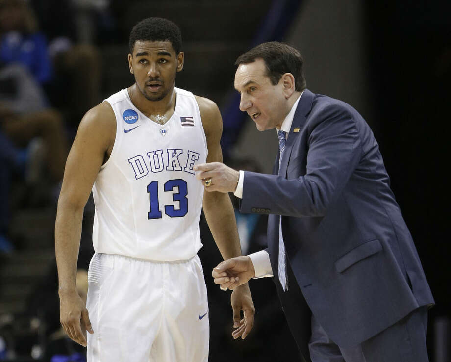 Duke head coach Mike Krzyzewski, right, talks with Duke's Matt Jones during the first half of an NCAA tournament college basketball game against Robert Morris in the Round of 64 in Charlotte, N.C., Friday, March 20, 2015. (AP Photo/Gerald Herbert)