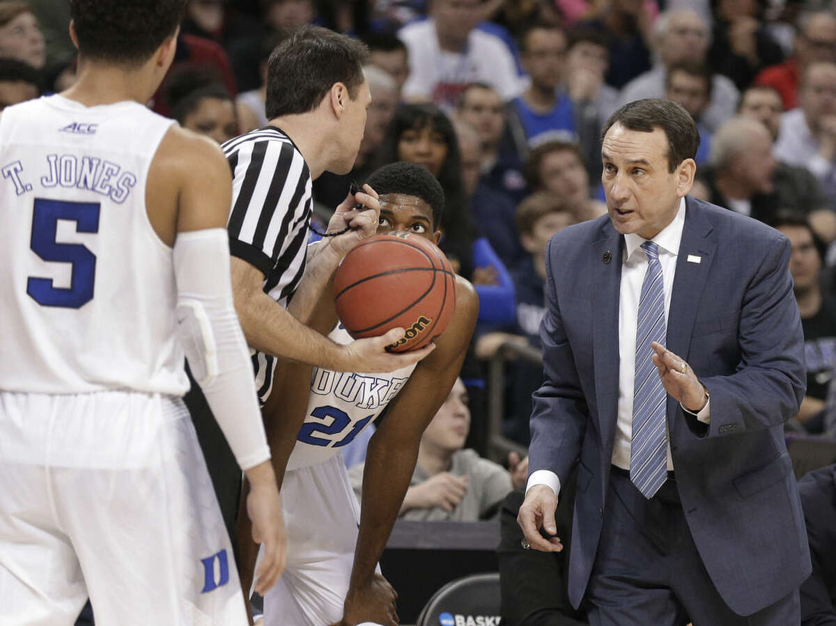 Duke head coach Mike Krzyzewski, right, talks to a referee during the first half of an NCAA tournament college basketball game against Robert Morris in the Round of 64 in Charlotte, N.C., Friday, March 20, 2015. (AP Photo/Nell Redmond)