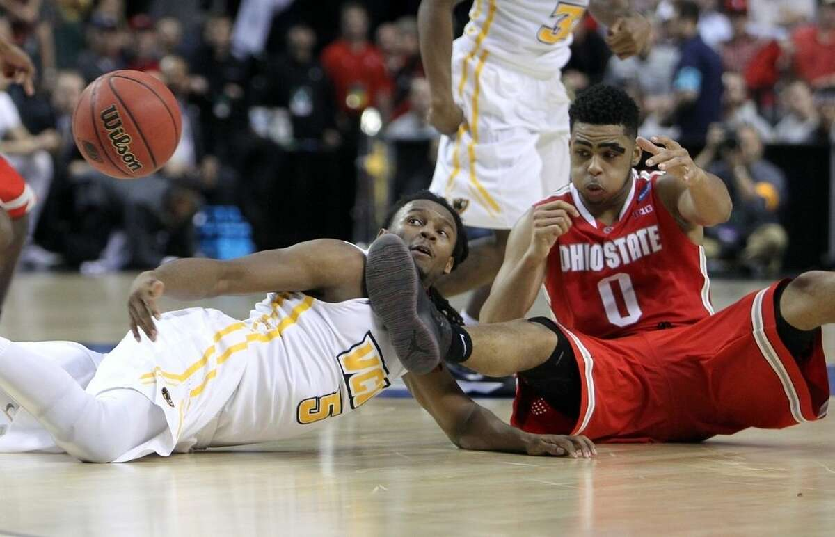 Ohio State guard D'Angelo Russell, fights for the ball with Virginia Commonwealth guard Doug Brooks during overtime of an NCAA college basketball second-round game in Portland, Ore., Thursday, March 19, 2015. (AP Photo/Craig Mitchelldyer)