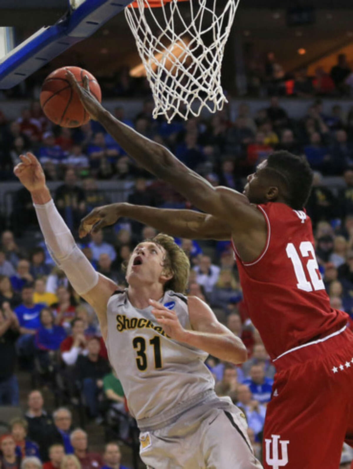 Indiana's Hanner Mosquera-Perea (12) fouls Wichita State's Ron Baker (31) during the first half of an NCAA tournament college basketball game in the Round of 64 in Omaha, Neb., Friday, March 20, 2015. (AP Photo/Nati Harnik)