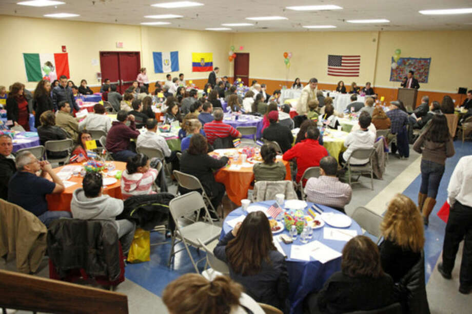 """Hour photos / Danielle CallowayCommunity members fill the room for a Latino community forum, """"Latinos Unidos de Connecticut,"""" urging the community to """"stand united for a cause,"""" at the South Norwalk Community Center Sunday afternoon. Below, President Gustavo Salas speaks at the forum."""