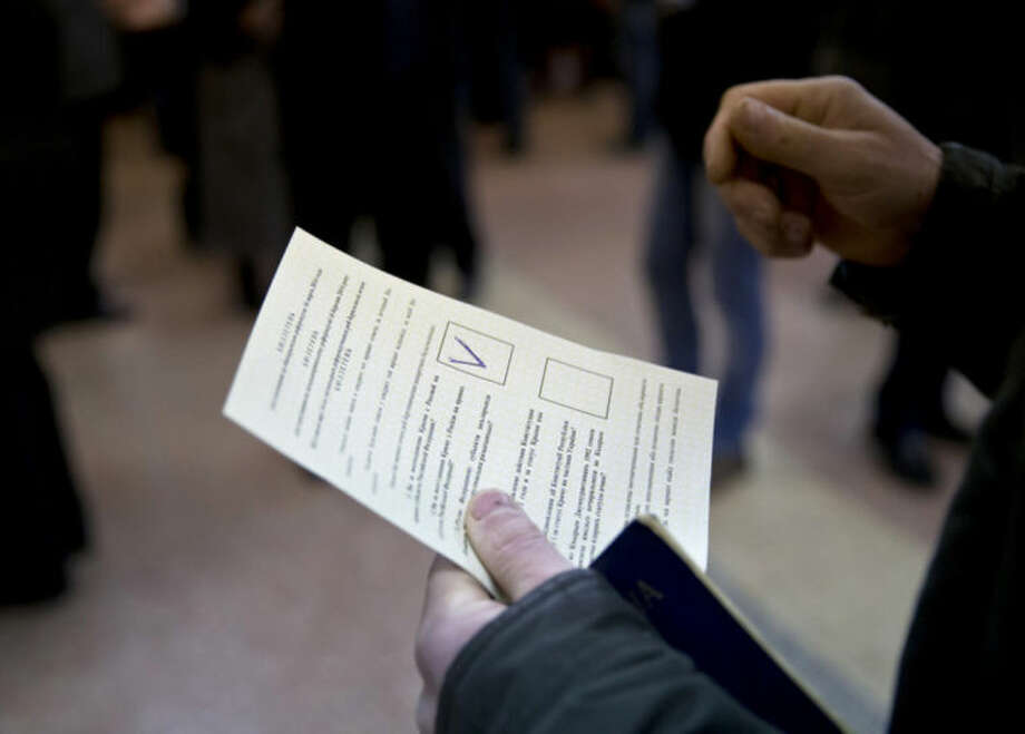 A man holds a ballot after casting a vote in favor of separation from Ukraine in the Crimean referendum in Simferopol, Ukraine, Sunday, March 16, 2014. Residents of Ukraine's Crimea region are voting in a contentious referendum on whether to split off and seek annexation by Russia. (AP Photo/Vadim Ghirda)