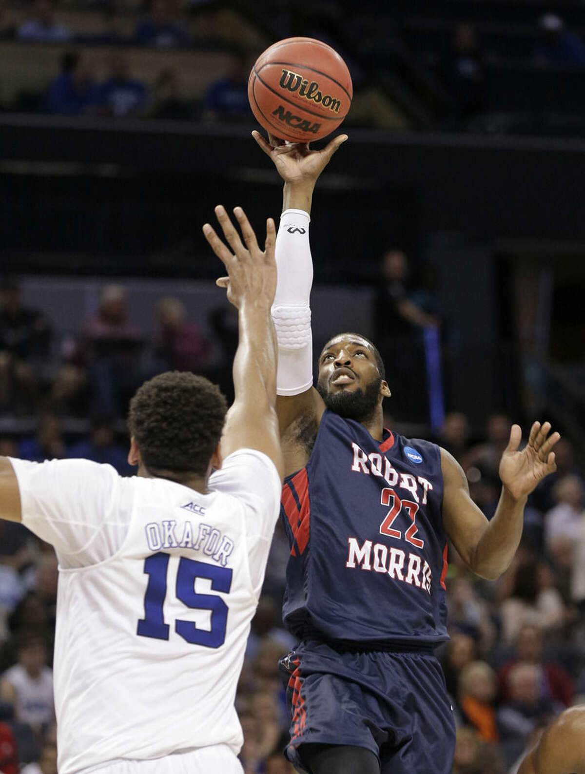 Robert Morris's Lucky Jones (22) shoots over Duke's Jahlil Okafor (15) during the first half of an NCAA tournament college basketball game in the Round of 64 in Charlotte, N.C., Friday, March 20, 2015. (AP Photo/Nell Redmond)