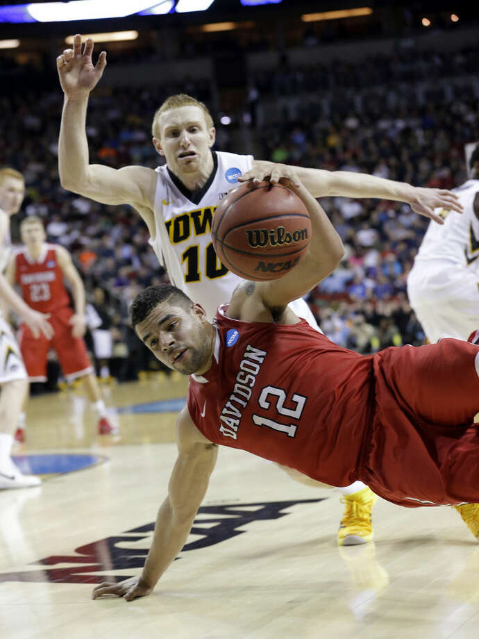 Davidson's Jack Gibbs (12) continues to dribble as he tumbles to the floor in front of Iowa's Mike Gesell during the second half of an NCAA tournament college basketball game in the Round of 64 in Seattle, Friday, March 20, 2015. (AP Photo/Elaine Thompson)